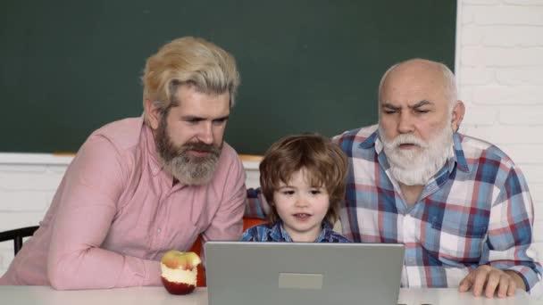 Heimatpädagogisches Konzept. Online lernen. Vater, Großvater und Sohn lernen zu Hause und machen Hausaufgaben.
