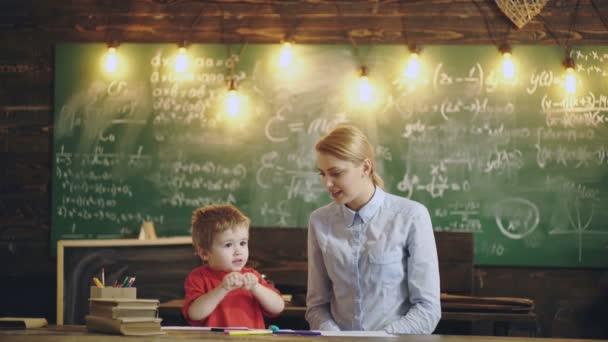 ZŠ a předškolák. Nadšená mladá matka a malý předškolák syn hrát a kreslit dohromady. Happy maminka učení s malým chlapcem dítě ve škole, vzdělávání koncept.