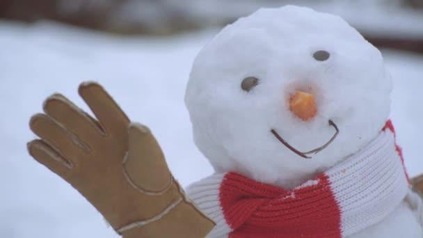 Közelkép hóember áll a téli sál piros orral. Holly vidám szajré karácsony és noel.