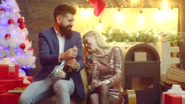 Šťastný Nový rok. Muž otvírá láhev šampaňského u vánočního stromku doma. Mladý milující pár těší na Vánoce.