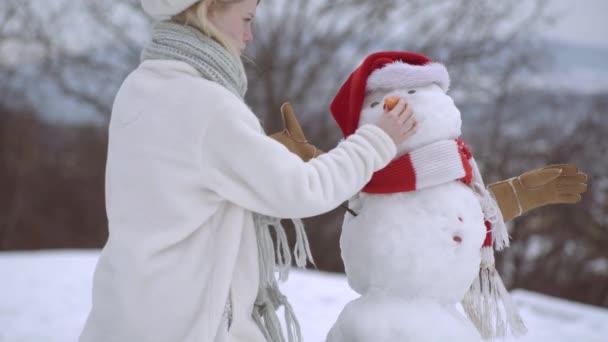 Detailní záběr veselé mladé ženy sněhuláka na sněhu kopce. Vtipný sněhulák s mrkvovým nosem. Zimní zábava a volný čas dovolená.