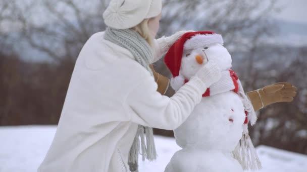 Boldog fiatal nő, aki jól érzi magát télen. Hóember és vicces lány. Csinálj hóembert!.