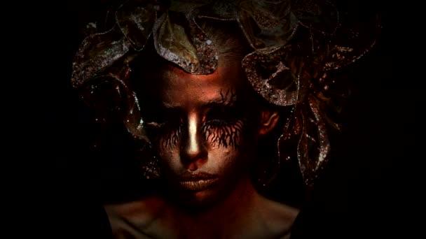 Fantazie. Kreativní umělecký projekt. Zlatá mladá žena. Halloweenská modelka, tvář ve zlatě. Halloween módní make-up. Dámská zlatá tvář.