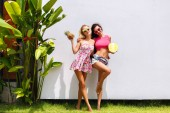Nyári szabadtéri nyaralás portréja két lenyűgöző legjobb meg lányok gyümölcsökkel