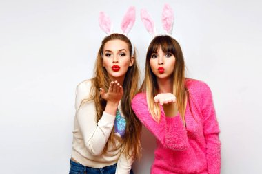 Close up fashion lifestyle portrait of two young hipster girls best friends in ears hairbands posing in studio blowing kisses