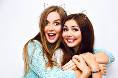 Close up fashion lifestyle portrait of two young hipster girls best friends posing in studio