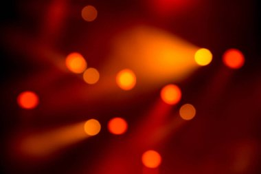 Abstract magic image with rays of colored light from floodlights in the dark and red bokeh photo