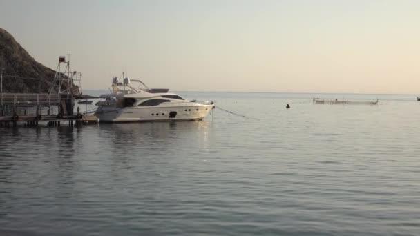 Luxusní bílá jachta kotvící v osamělém přístavu při západu slunce. Moře je klidné, bez vln. Paprsky zapadajícího slunce se odrážejí na hladkém povrchu vody. Panorama a hory jsou viditelné