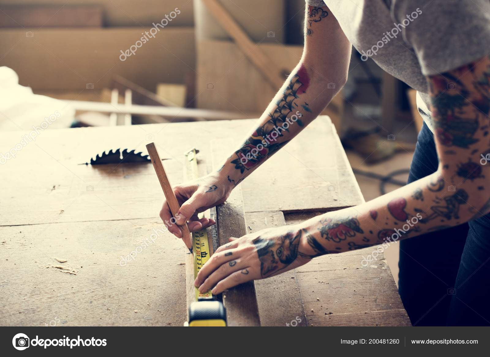 0e12066ba Partial view of female carpenter with tattoos using pencil and measurement  tape on wood — Photo by Rawpixel