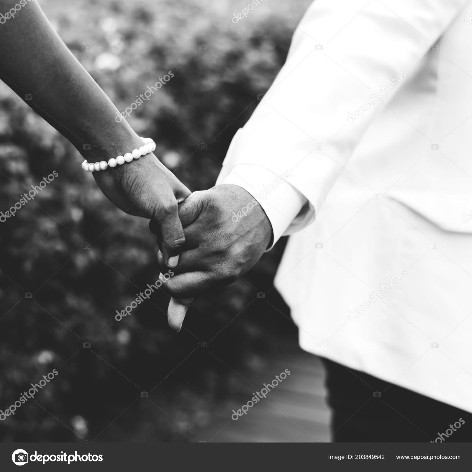 Black and white cropped shot of wedding couple holding hands stock image