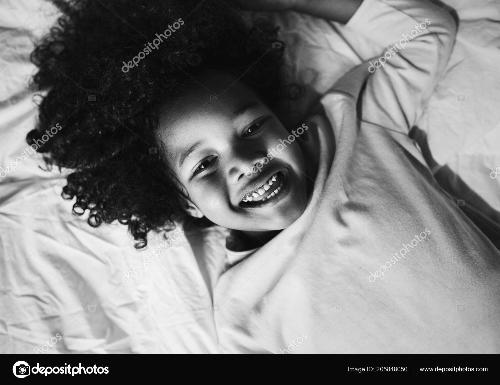 African child enjoying smiling bed stock photo