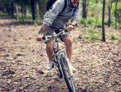 člověk jezdit na horském kole v lese