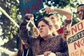 Fotografie Closeup of angry teen girl protesting demonstration holding posters antiwar justice peace concept