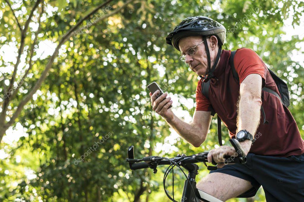 Senior cyclist using gps on mobile phone