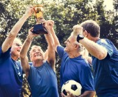 Fotografie Team of mature football players winning the cup