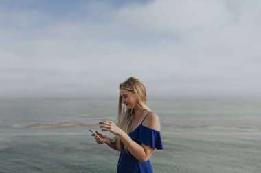 blond woman listening to music at a beach