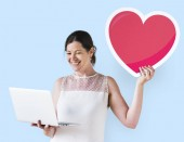 Fotografie Woman holding a heart emoticon and a laptop