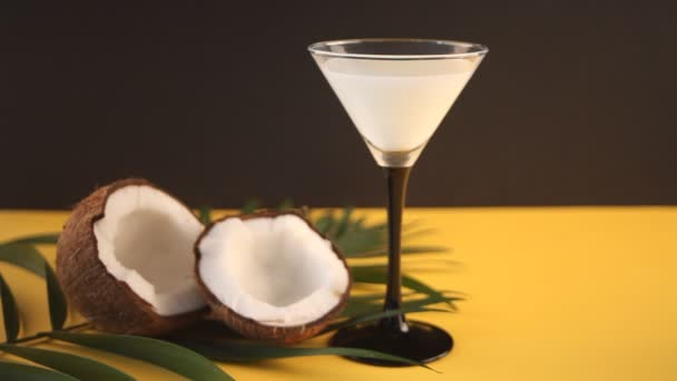 Pina Colada Cocktail, sweet cocktail made with rum, coconut cream or coconut milk on yellow table and black background. Woman hand puts the second glass with drink on the table.