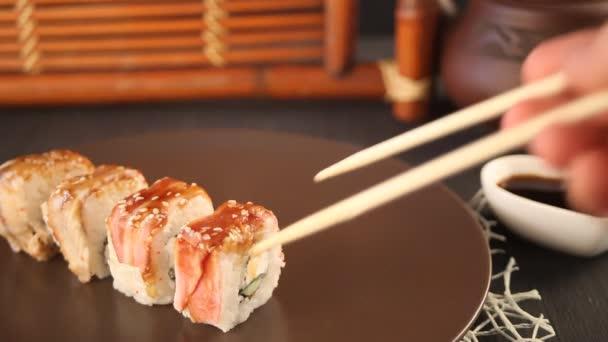 Női kéz pálcika mártással sushi tekercs a szójaszósz.