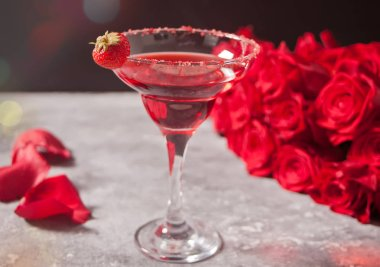 Red exotic alcoholic cocktail in clear glass and red roses for romantic dinner.