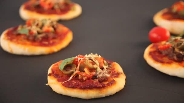 Ženská ruka položila na černou desku domácí Mini pizzu. Malá pizza korunka s šunkou, zelenými olivami, třešňovou rajčaty a čerstvou bazalka. Domácí jídlo. Koncept pro chutné a vydatné jídlo. Zavřít.