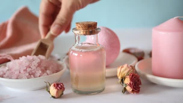 Růžová koupel sůl a produkty pro péči o tělo s růžovými růžemi. Kosmetická léčba. Lázeňský relax koncept. Žena ruka míchání sůl s dřevěnou lžičkou