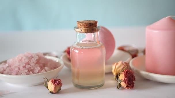Růžová koupel sůl a produkty pro péči o tělo s růžovými růžemi. Kosmetická léčba. Lázeňský relax koncept. Žena položila na stůl růžový ručník.