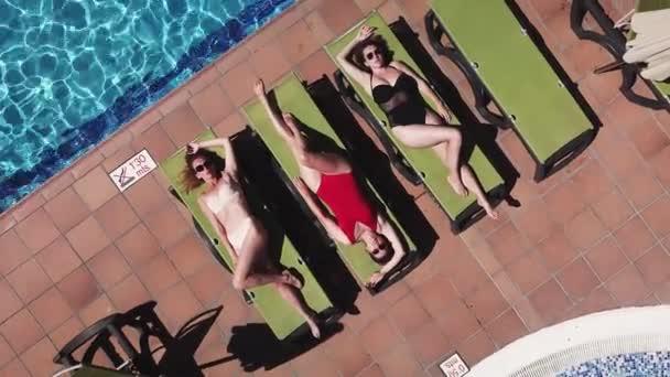 Légi felvétel három lány fekszik a nap alatt, közel a medencéhez