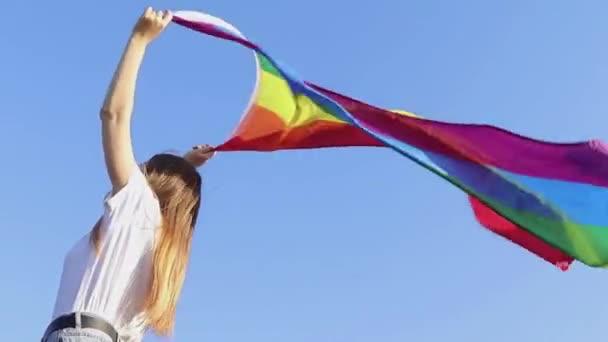 Mladá žena rozvíjí duhovou vlajku proti obloze na podporu komunity LGBT. Koncept volné lásky, rovnost práv, lesbičky, LGBTQI, Pride Event, LGBT Pride Month. Ukrajinská dáma