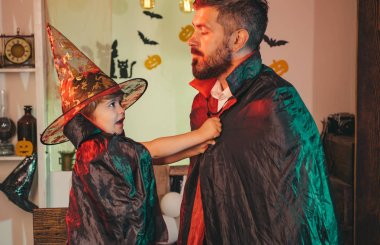 Wizard party. Boy puts a superhero overcoat on a bearded man. Father and son play together in a fabulous wizard. Funny masquerade weekend. Costume Party.