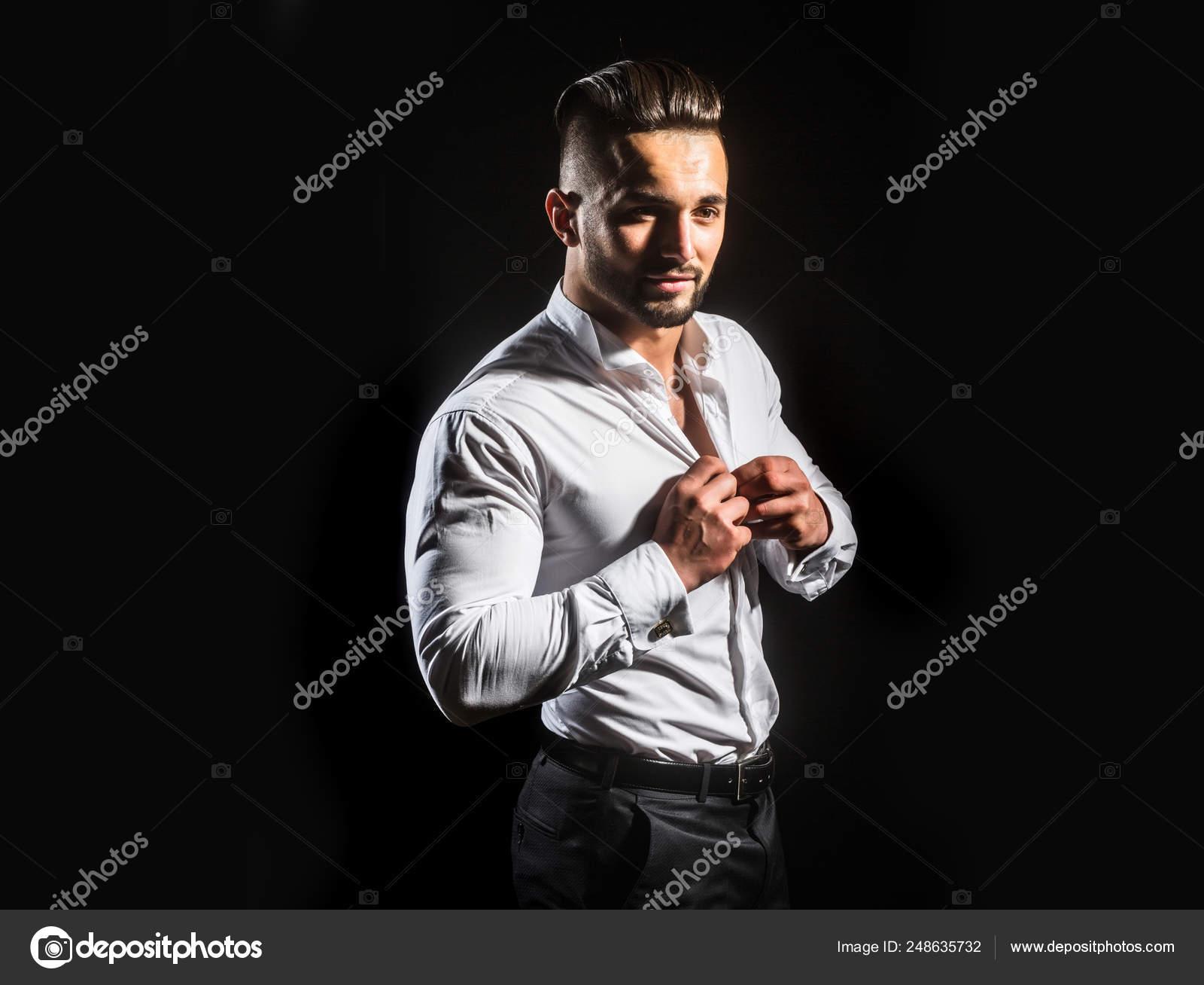 76dfd79822 Botones de una camisa blanca. Hombre botones hasta su posición de camisa  blanca sobre fondo negro. Hombre de negocios piensa en negocios por la  mañana.
