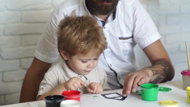 Festés. Kreatív oktatás. Apa és fia együtt rajzolnak. Tanár és diák a kreativitás óráin. Álmodj otthon.