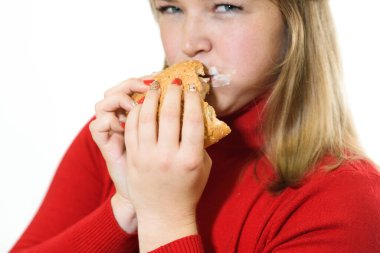Young fat girl on a white background eats a burger. Studio shot