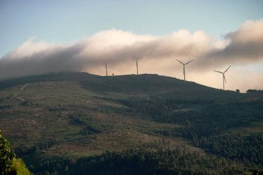 green mountain landscape with electric windmills and fog
