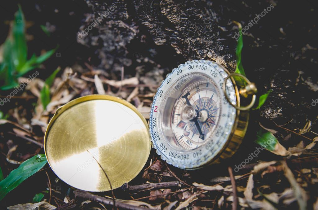 Antique brass compass over wooden background (vintage)