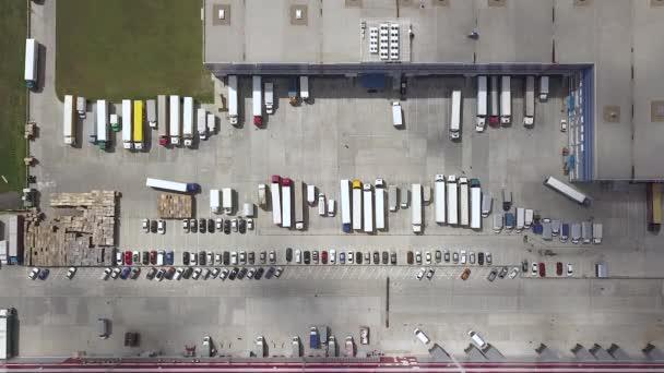 Letecký pohled shora dolů na nákladní automobily, kontejnery a distribuční sklad.