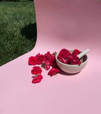 Pestle and white mortar filled with bright red roses on a pink background