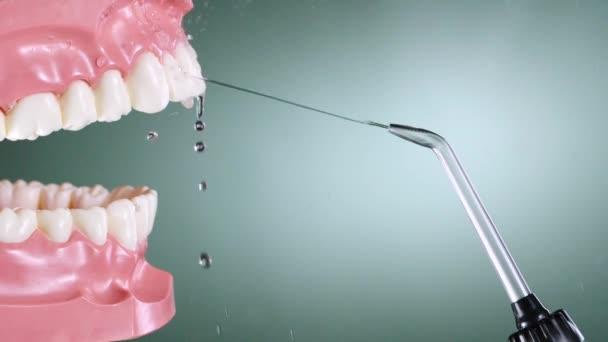 Water flosser cleaning teeth on green