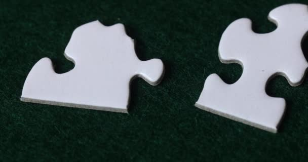 Hands putting together white pieces of jigsaw puzzle on green felt.