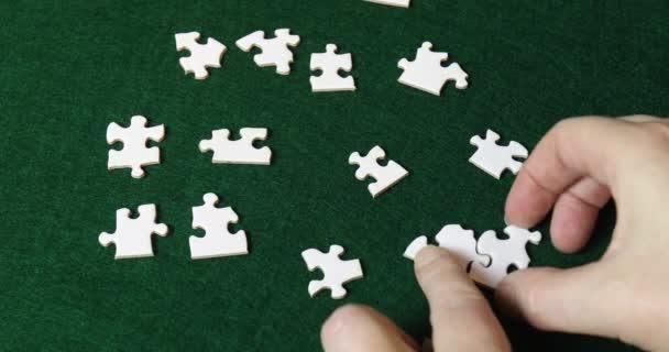 Bílé ruce dávat dohromady kousky skládačky puzzle na zelené plsti.