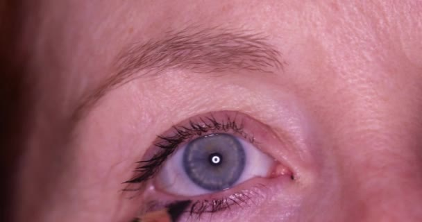 Macro of woman applying eye liner around blue eyes.
