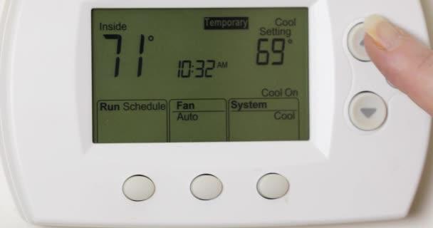 Nahaufnahme von Hand Erhöhung der Temperatur am elektrischen Thermostat, um Energie in der Sommerklimatisierung zu sparen.