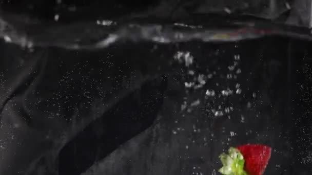 Erdbeerfrüchte planschen unter Wasser in Tank mit Blasen.