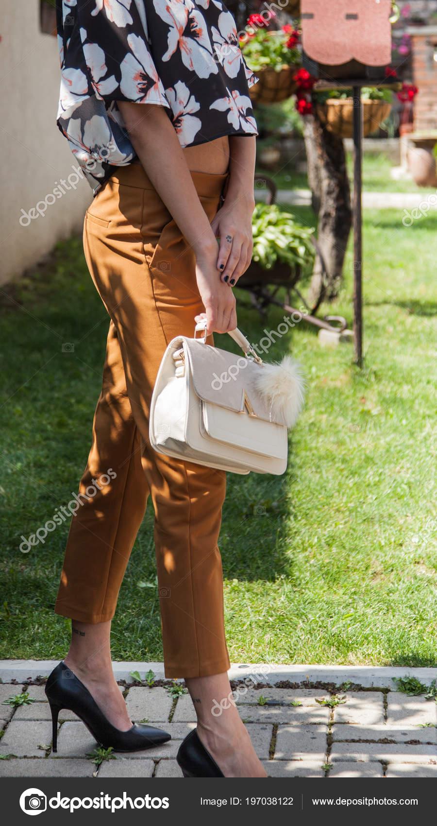 Νεαρό ελκυστική γυναίκα μοντέλο με μακριά πόδια σε μαύρο ψηλά τακούνια που  φορούσε καφέ παντελόνι και κενταύριο-πουκάμισο με λουλούδι designe σε αυτό  ... a89bf2fe761