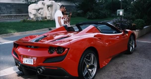 Monte Carlo, Monako - 7. července 2020: Muž a žena vedle jejich Ferrari super sportovní auto