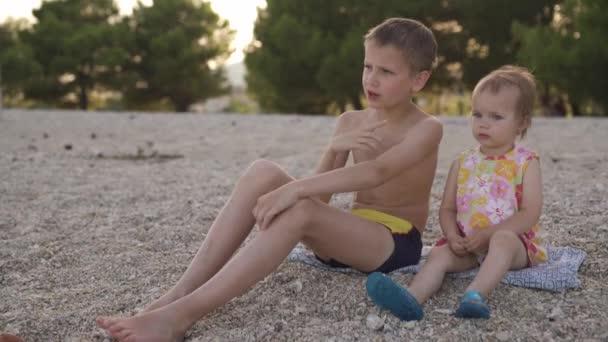 Junge und Mädchen sitzen am Strand. Bruder und jüngere Schwester ruhen am Meer. Emotionen, Liebe, Zärtlichkeit,