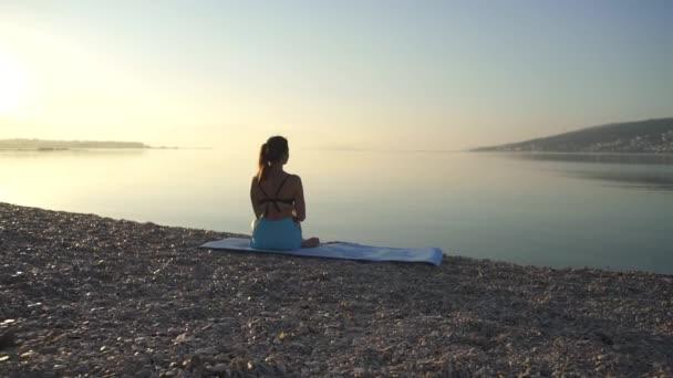 Schöne Mädchen wärmt sich auf und praktiziert Yoga am Meer. Sport, Yoga, Strand, Zeitlupe.