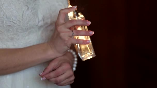 Bride spraying perfume on her wrist. Focus on hands and perfume bottle.