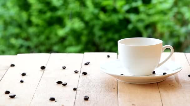 Kávová zrnka na dřevěné desce v blízkosti šálku kávy