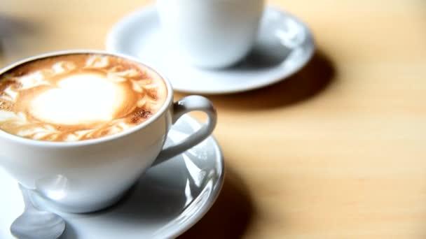 Při posouvání horké kávy na stole/teplé cappuccino s pěknou mléčnou pěnou